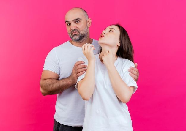 Volwassen paar strikte man die vrouw door schouders houdt en kijkt en zij bekijkt hem en doet kusgebaar