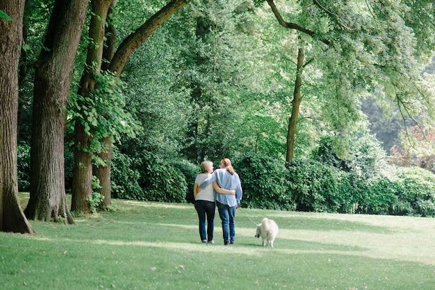 Volwassen paar wandelen op het gras met een witte hond