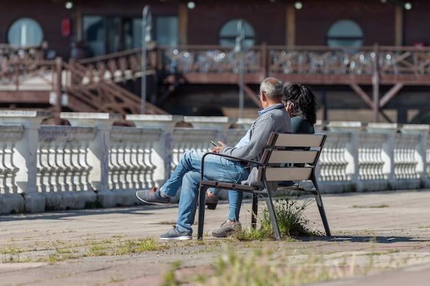 Volwassen paar zittend met telefoons op een bankje in een achteraanzicht van het stadspark