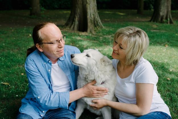 Volwassen paar zittend op het gras met een witte hond