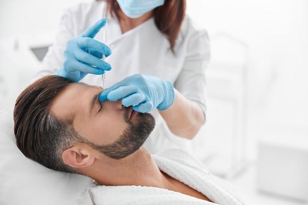 Volwassen persoon ondergaat neusbrugvullerprocedure met professionele schoonheidsspecialiste in de kliniek