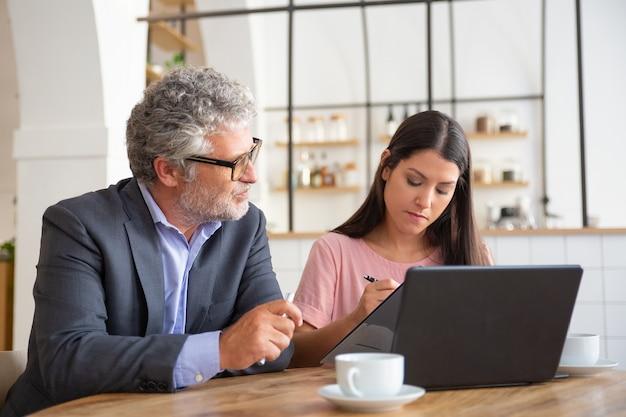 Volwassen professionele en jonge klant ondertekening overeenkomst