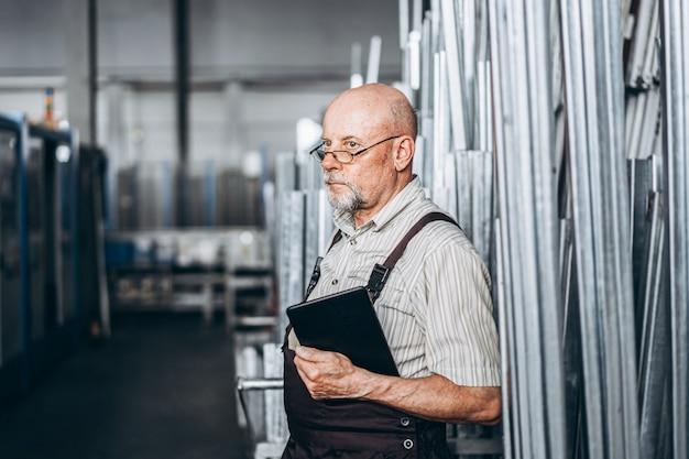 Volwassen professionele werknemer op de fabriek die met machines werkt.