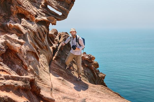 Volwassen reiziger fotograaf klimt op rotsen boven zee, hormuz island, hormozgan, iran.