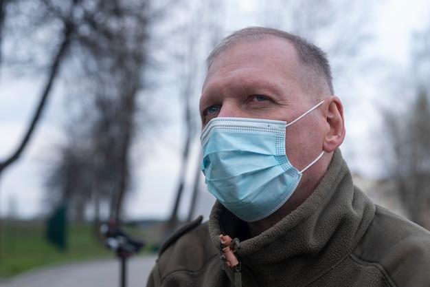 Volwassen senior man alleen in park in blauw gezichtsmasker.