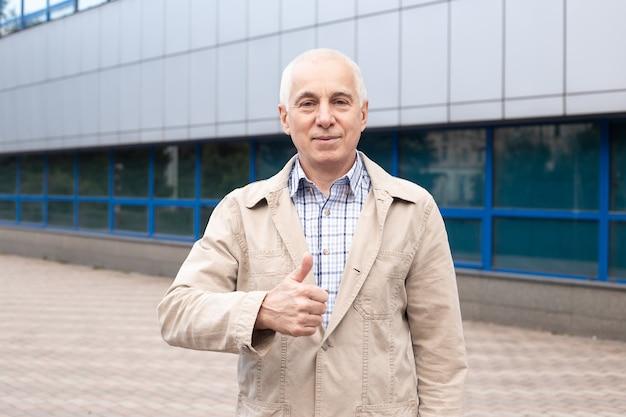 Volwassen senior man duimen opdagen buiten in stad landschap in de buurt van kantoorgebouwen