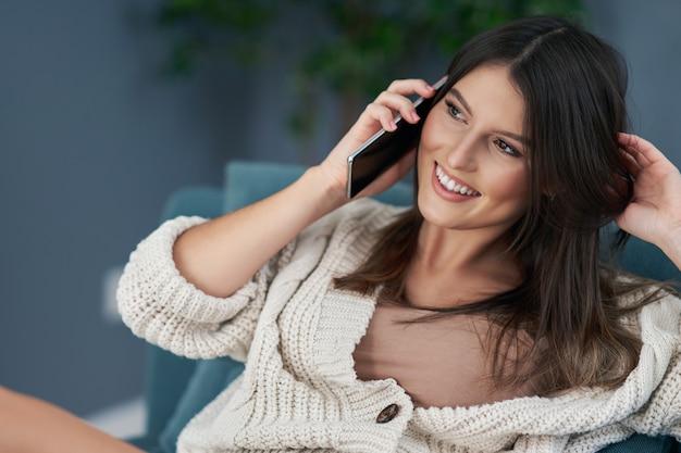 Volwassen sexy vrouw die thuis ontspant en smartphone gebruikt