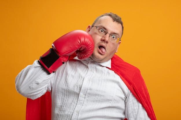 Volwassen slavische superheld man in rode cape bril en doos handschoenen kijken kant slaan zichzelf in gezicht met tong teruggetrokken geïsoleerd op oranje muur