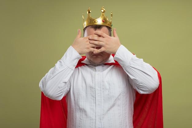 Volwassen slavische superheldenmens in rode cape die glazen en kroon dragen die ogen bedekken met handen die op olijfgroene muur worden geïsoleerd