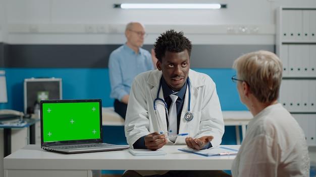 Volwassen specialist in gesprek met patiënt met horizontaal groen scherm