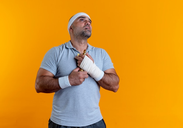 Volwassen sportieve man in hoofdband knuffelen zijn trofee opzoeken met hoop expressie staande over oranje muur