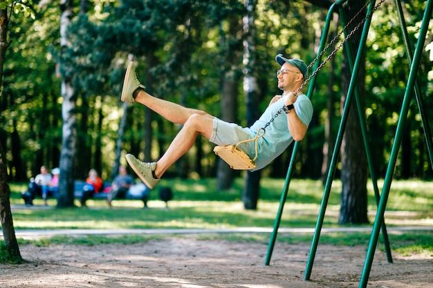 Volwassen stijlvolle man in glazen rijden op schommel in stadspark op speelplaats voor kinderen in de zomer.