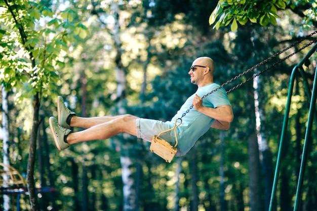 Volwassen stijlvolle man in glazen rijden schommel in stadspark in de zomer.