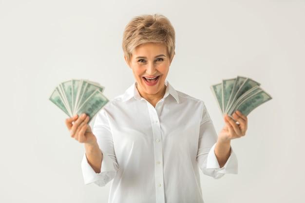 Volwassen stijlvolle vrouw in een wit overhemd op een witte achtergrond met dollars in haar hand