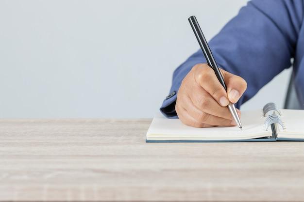 Volwassen student universitaire studie in de klas en handnota lezing in open notitieboekje voor examen. volwasseneneducatie is de praktijk om systematische, aanhoudende zelfeducatieve activiteiten te ontplooien in nieuwe kennisvaardigheden