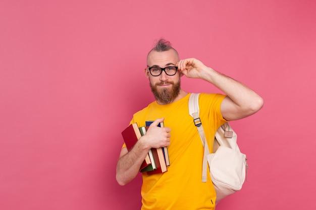 Volwassen student vrolijke vrijetijdskleding man met baard en rugzak met boeken geïsoleerd op roze