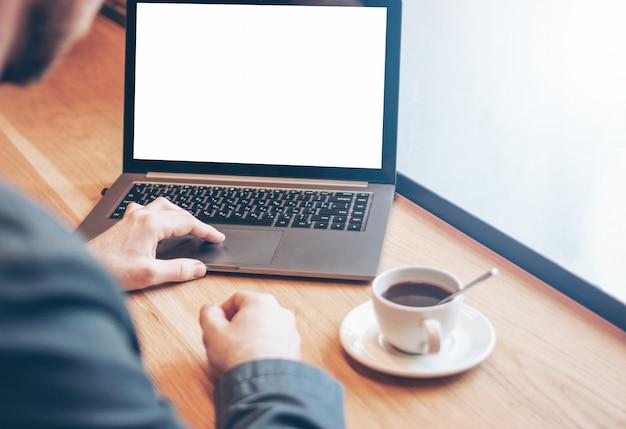 Volwassen succesvolle kale bebaarde man in pak met laptop in café