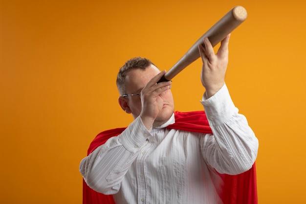 Volwassen superheld man in rode cape bril houden honkbalknuppel voor oog gebruiken als telescoop geïsoleerd op oranje muur