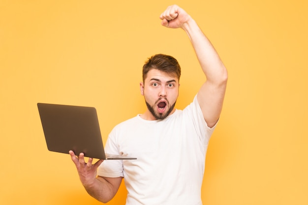 Volwassen tiener met een laptop in zijn handen gewonnen, verheugt zich in de overwinning met zijn opgeheven hand