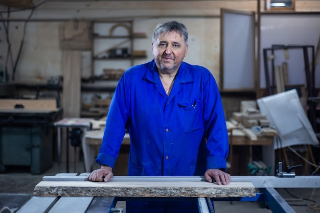 Volwassen timmerman nadert de camera en staat in een zelfverzekerde houding in zijn atelier