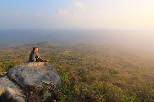 Volwassen toerist in zwarte broek, jas en donkere pet zit op de rand van de klif en kijkt naar mistige heuvelachtige vallei