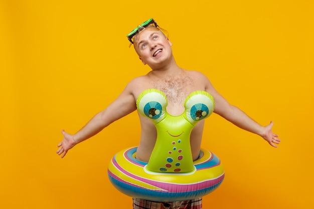 Volwassen topless man in rubberen ringvorm van slak en duikbril poseren
