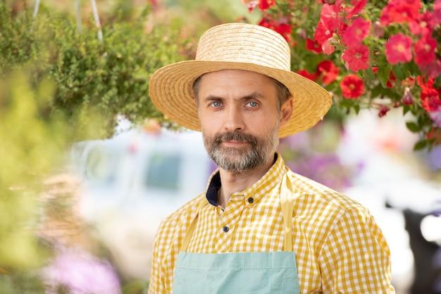 Volwassen tuinman in hoed en schort staande onder bloemen in bloei tijdens het werken in kas