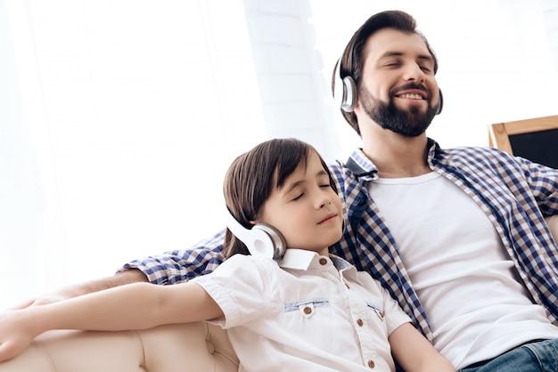 Volwassen vader en tiener die aan muziek op hoofdtelefoons luisteren.