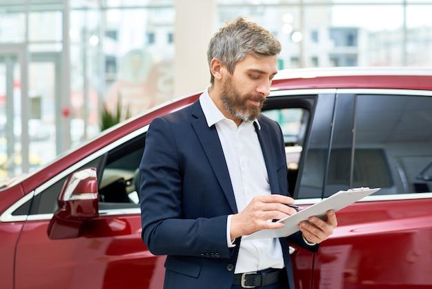 Volwassen verkoopassistent in autoshowroom