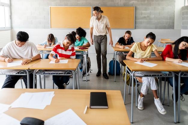 Volwassen volwassen blanke man leraar wandelen in de klas om multiraciale groep studenten te controleren die een examen afleggen. onderwijsconcept.