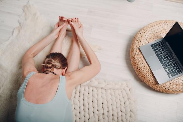 Volwassen volwassen vrouw die yoga doet in de woonkamer thuis met online tutorials op laptop
