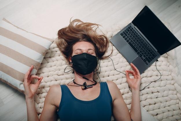 Volwassen volwassen vrouw die yoga nidra doet en in een gezichtsmasker thuis in de woonkamer ligt met online tutorials op laptop.