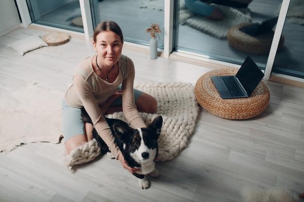 Volwassen volwassen vrouw doet yoga thuis in de woonkamer met corgi hond huisdier met online tutorials op laptop