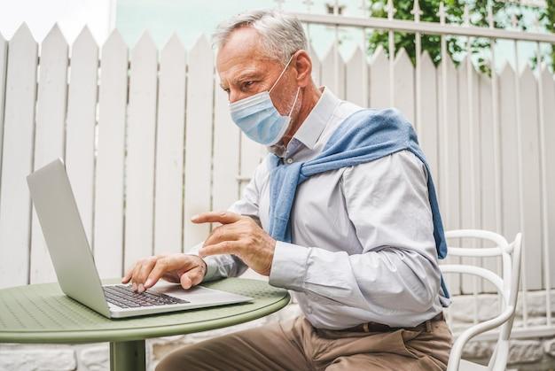 Volwassen volwassene die zijn computerlaptop gebruikt bij het terras