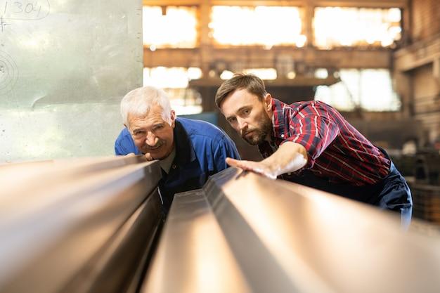 Volwassen voorman en zijn ondergeschikte in werkkleding kijken naar nieuwe metalen werkstukken of details voor industriële machines