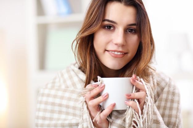 Volwassen vrouw bedekt met deken die griep heeft