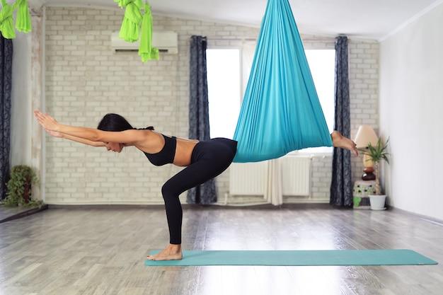 Volwassen vrouw beoefent anti-zwaartekracht yoga