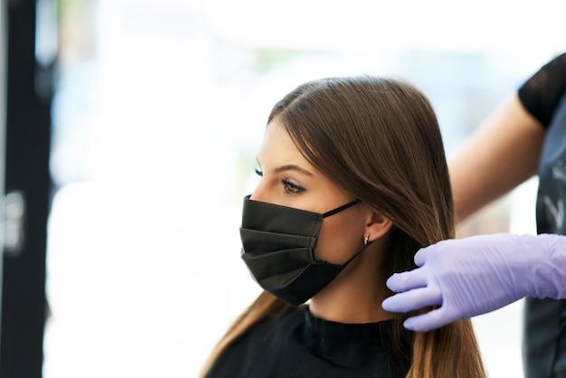 Volwassen vrouw bij kapper die een beschermend masker draagt als gevolg van een pandemie van het coronavirus