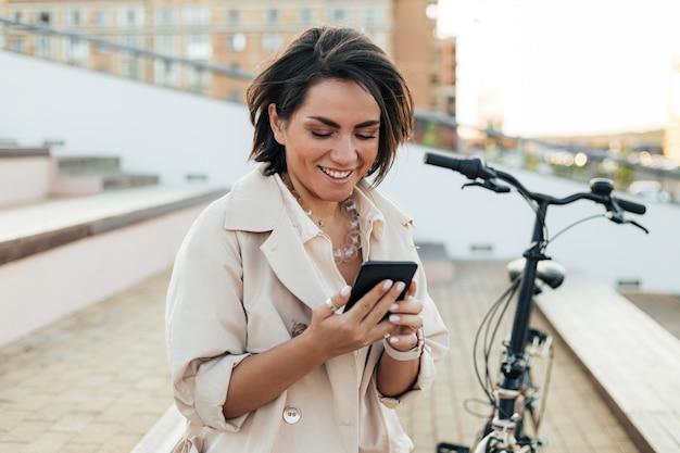 Volwassen vrouw buitenshuis doorbladeren telefoon