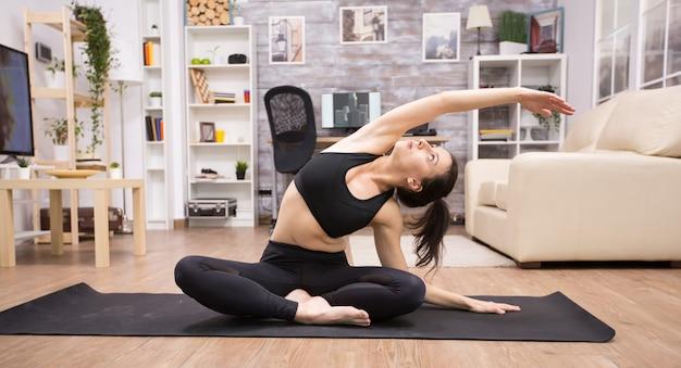 Volwassen vrouw concentreerde zich op haar adem terwijl ze thuis yoga deed.