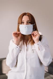 Volwassen vrouw die beschermend masker draagt, dat op grijze achtergrond wordt geïsoleerd. coronavirus pandemie - covid-19. reclame voor medische maskers
