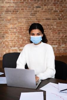 Volwassen vrouw die een gezichtsmasker draagt op kantoor