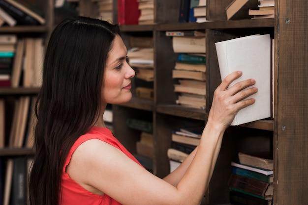 Volwassen vrouw die een roman van de boekenrekken neemt