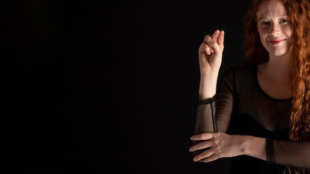 Volwassen vrouw die gebarentaal met exemplaarruimte onderwijst
