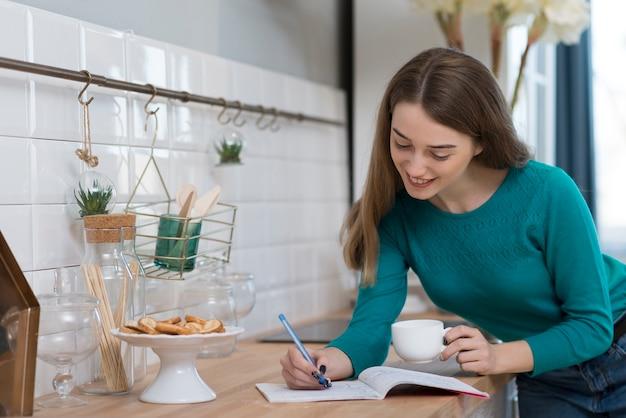 Volwassen vrouw die haar huiswerk in de keuken doet