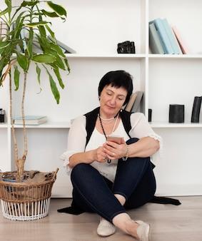 Volwassen vrouw die haar telefoon bekijkt