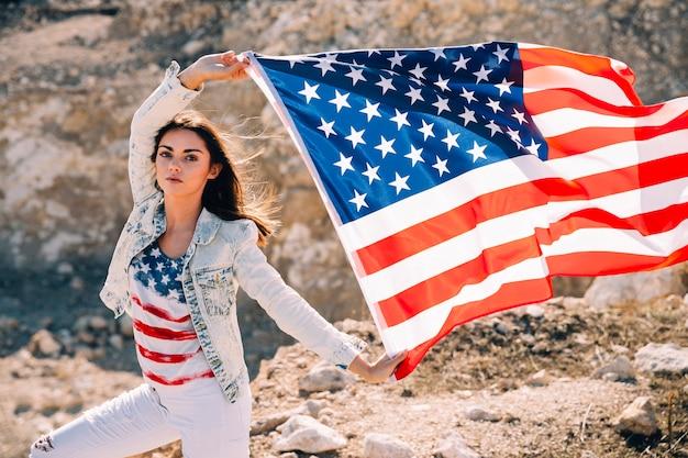 Volwassen vrouw die handen met de vlag van de vs opheffen