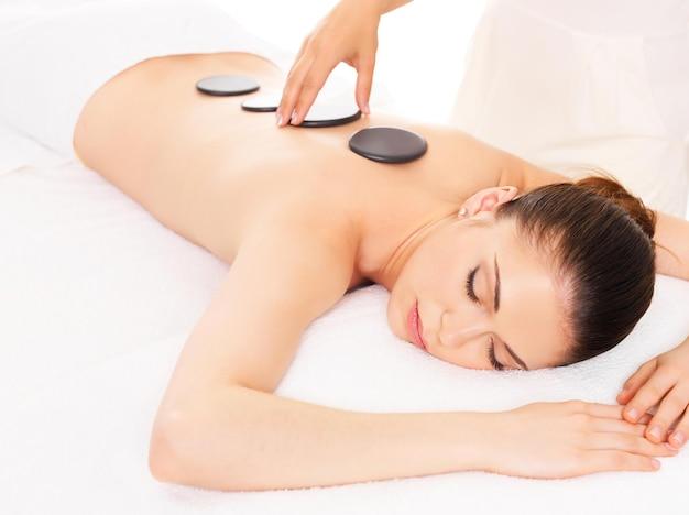 Volwassen vrouw die hete steenmassage in kuuroordsalon heeft. schoonheidsbehandeling concept.