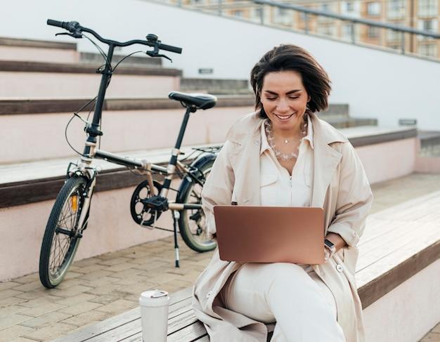 Volwassen vrouw die laptop buitenshuis doorbladert