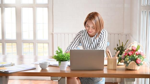 Volwassen vrouw die met digitale tablet en pen werkt.
